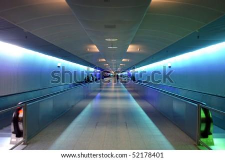 Illuminated walkway through modern airport in Germany - stock photo