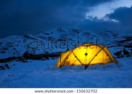 illuminated yellow tent in a wintry blue cold landscape - stock photo