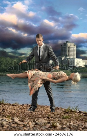 Illusionist. A handsome confident man keeps a young lady levitating in the air. - stock photo