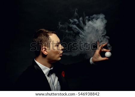 Illusionist man makes smoke his hand on a dark background.