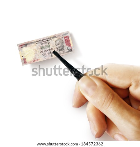 Illustration for inflation - hand with a pincer holding small banknote of Indian rupee, white background - stock photo