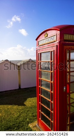 Illustration of a BT GPO red telephone box on a beach, created using median noise reduction - stock photo
