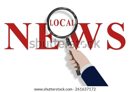 """Illustration of a hand holding a magnifying glass with the words """"Local News"""" - stock photo"""