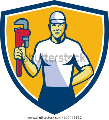 Illustration of a plumber wearing hat holding monkey wrench facing front set inside shield crest on isolated background done in retro style.