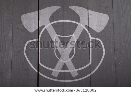 Illustration of fire man sign with helmet and axes on dark black wooden background - stock photo