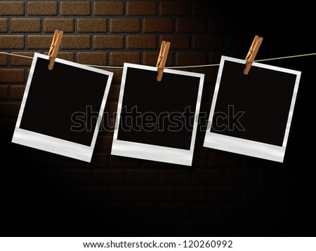 Illustration of old photos on a rope with clothespins in front of a brick wall background.