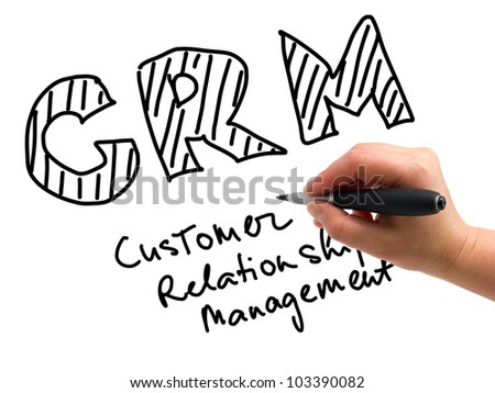 Illustration of the hand with a pen writing CRM on the white paper background - stock photo
