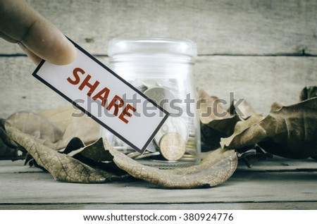 image concept cropped finger holding white card with black frame with word SHARE. background with coin in glass jar surrounded by dry leaves and wood. - stock photo