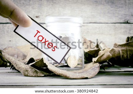 image concept cropped finger holding white card with black frame with word TAXES. background with coin in glass jar surrounded by dry leaves and wood. - stock photo