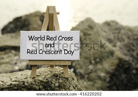 Image concept with word WORLD RED CROSS AND RED CRESCENT DAY on white canvas and easel. blurred rock image background at the shore