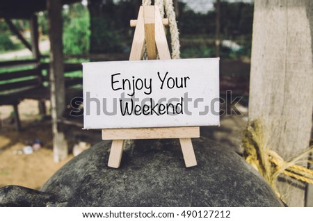 image concept, word ENJOY YOUR WEEKEND on white canvas and wooden easel over blurred background