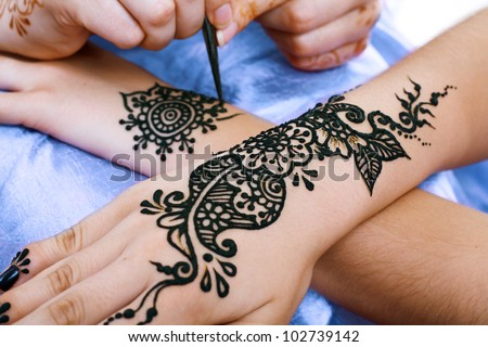 Image detail of henna being applied to hand