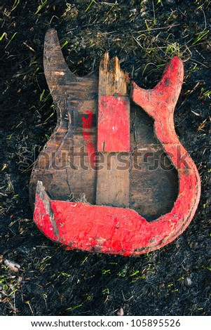 Image electric guitar, which was burned down, on the burned ground.