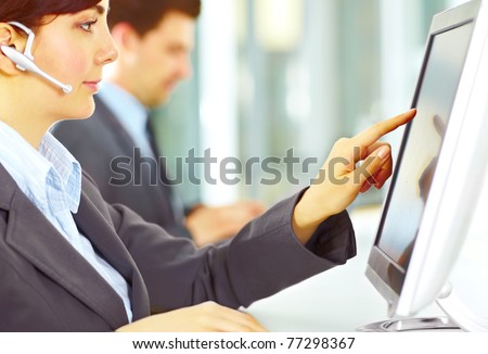 Image focused on hand of the customer support working in the office touching the screen - stock photo