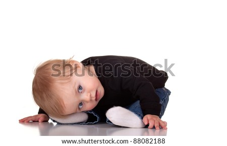 Image of a baby being cute laying with her head on her feet. - stock photo