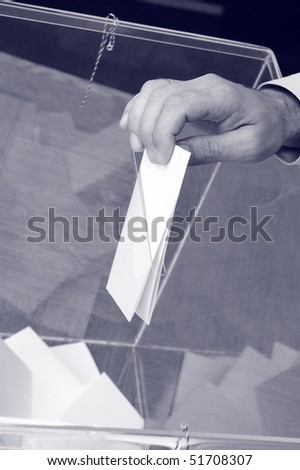 image of a ballot box and hand putting a blank ballot inside - stock photo