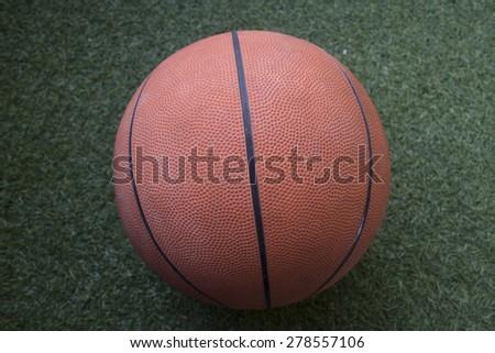 Image of a basketball lying on artificial turf - stock photo
