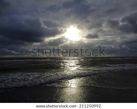 Image of a Beach Sunset Breaking through Clouds  - stock photo