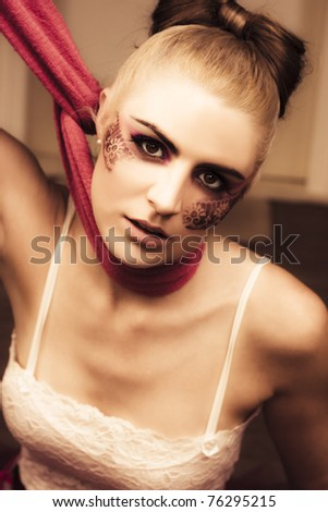 Image Of A Beautiful Glamour Fashion Model With Fine Art Lace Makeup Pulling Neck Scarf Tight In A Clothing Control Or Fashion Victim Conceptual - stock photo