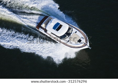 Image of a beautiful white and brown boat seen in the water from above - stock photo