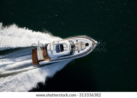 Image of a beautiful white and brown motor boat dashiong through a sea on a sunny day
