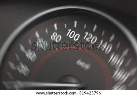 Image of a blurry speedometer from a car. The sharp number is 100 km/h. Image has a spin blur effect applied to create blurry feeling of speed.