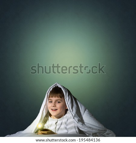 image of a boy under the covers with a flashlight - stock photo