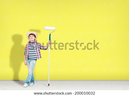 image of a boy with hat standing near the painted wall - stock photo