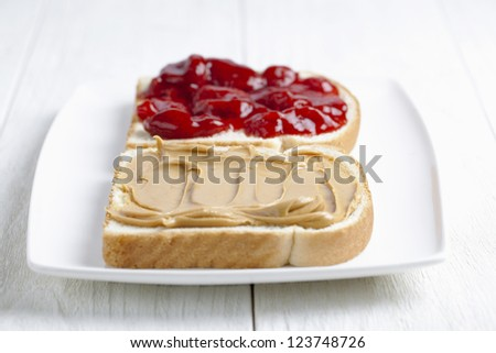 Image of a bread with a spread of butter and strawberry jam placed on the white plate - stock photo