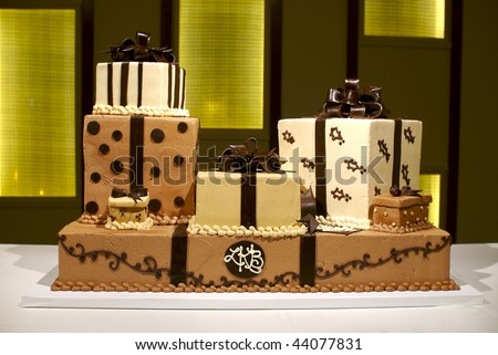 Image of a brown and white wedding cake with multiple layers, polka dots, and stripes - stock photo