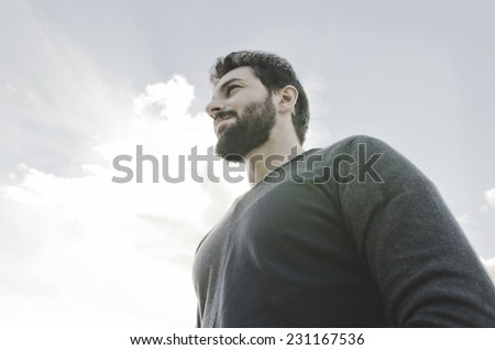 Image of a brunette bearded hipster looking to the sky in backlight shot - stock photo