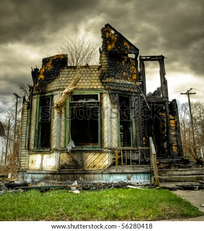 Image of a burned abandoned house in an urban setting with overcast sky. - stock photo