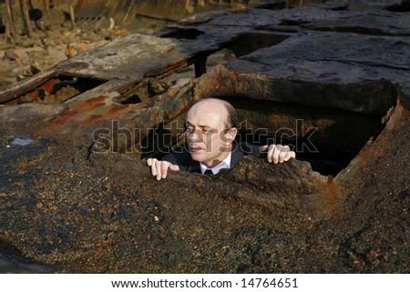 Image of a business man appearing out of a ship wreck hull. - stock photo