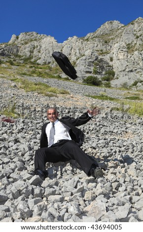 Image of a businessman in a difficult situation sliding on a rocky mountain slope.