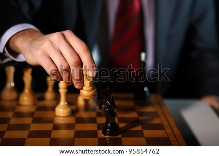Image of a businessman in dark suit playing chess - stock photo