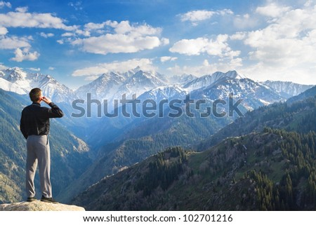 Image of a businessman standing on the top of the mountain, using a laptop, talks on the phone. In the background a beautiful panorama of the valley with high peaks.