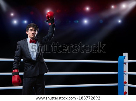 image of a businessman with boxing gloves in the ring, the competition in the business - stock photo