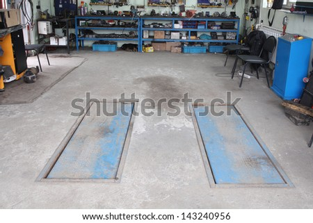 Image of a car repair garage with lift in non-working position - stock photo