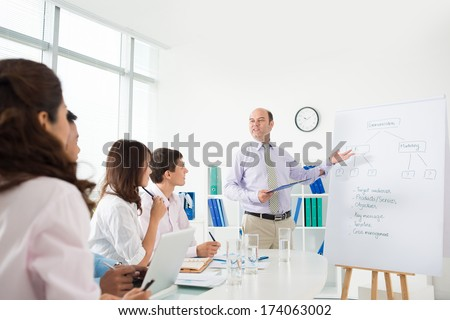 Image of a CEO explaining to his partners marketing process of the company on the foreground  - stock photo