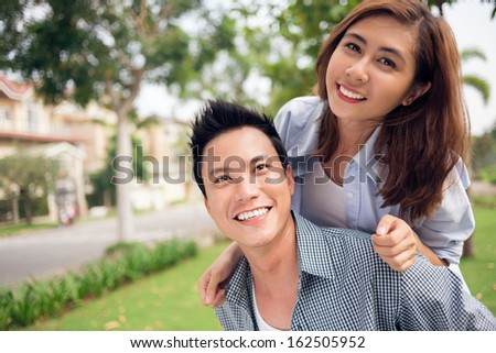 Image of a cheerful young couple piggybacking in the park  - stock photo