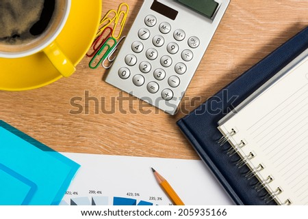 image of a cup of coffee, calculator, notepad and pencil. business still life