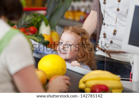 Image of a cute girl at the checkout counter in the supermarket. - stock photo