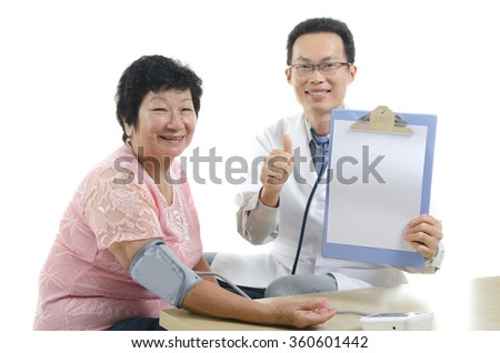 Image of a doctor and his nurse checking up a senior patient in the clinic