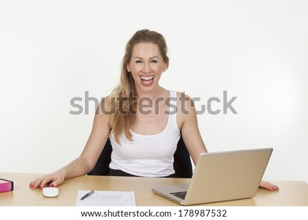 Image of a female business executive laughing loudly while working on the laptop, isolated on white background.
