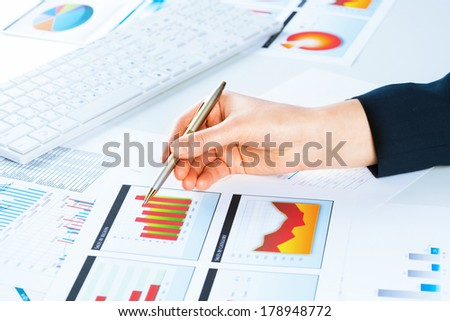 image of a female hand pointing to the financial growth charts