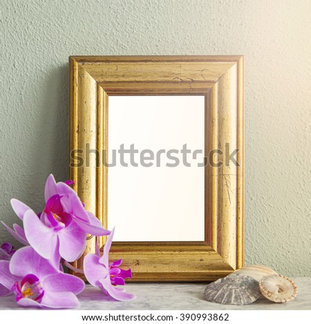 Image of a gilded frame mockup scene, with orchids and sea shells.  - stock photo