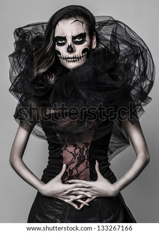 Image of a girl who is posing with a skull mask make up on the grey background - stock photo
