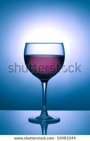 Image of a glass of dark wine silhouetted against a blue spotlight on dark background with reflection