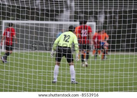 Image of a goalkeeper through the net, focus goalkeeper, rain all game - stock photo