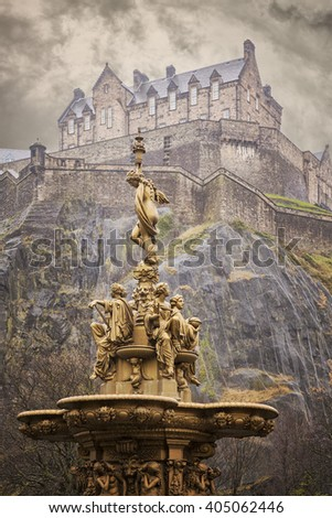 Image of a gold fountain in Princess Street gardens, Edinburgh. Above is Edinburgh castle.  - stock photo